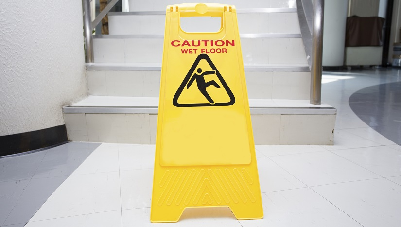 Image of wet floor sign at the bottom of a flight of white stairs