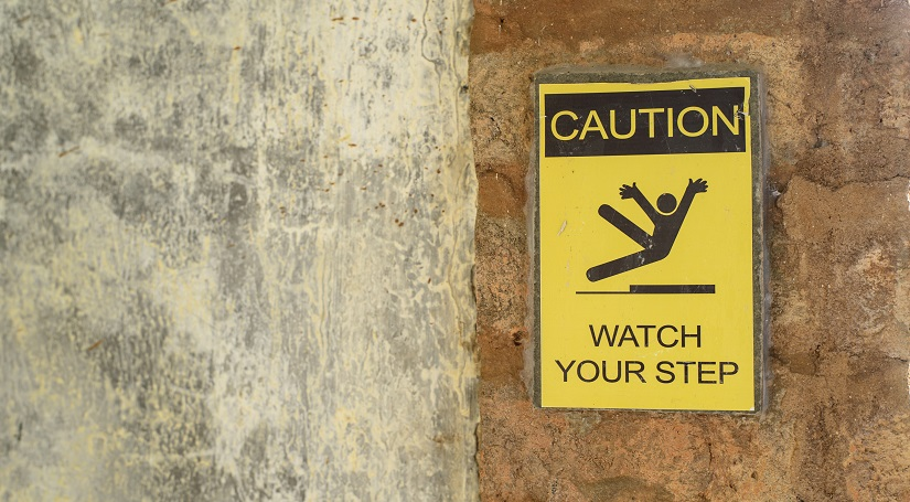Picture of a wall with a 'watch your step' sign on it