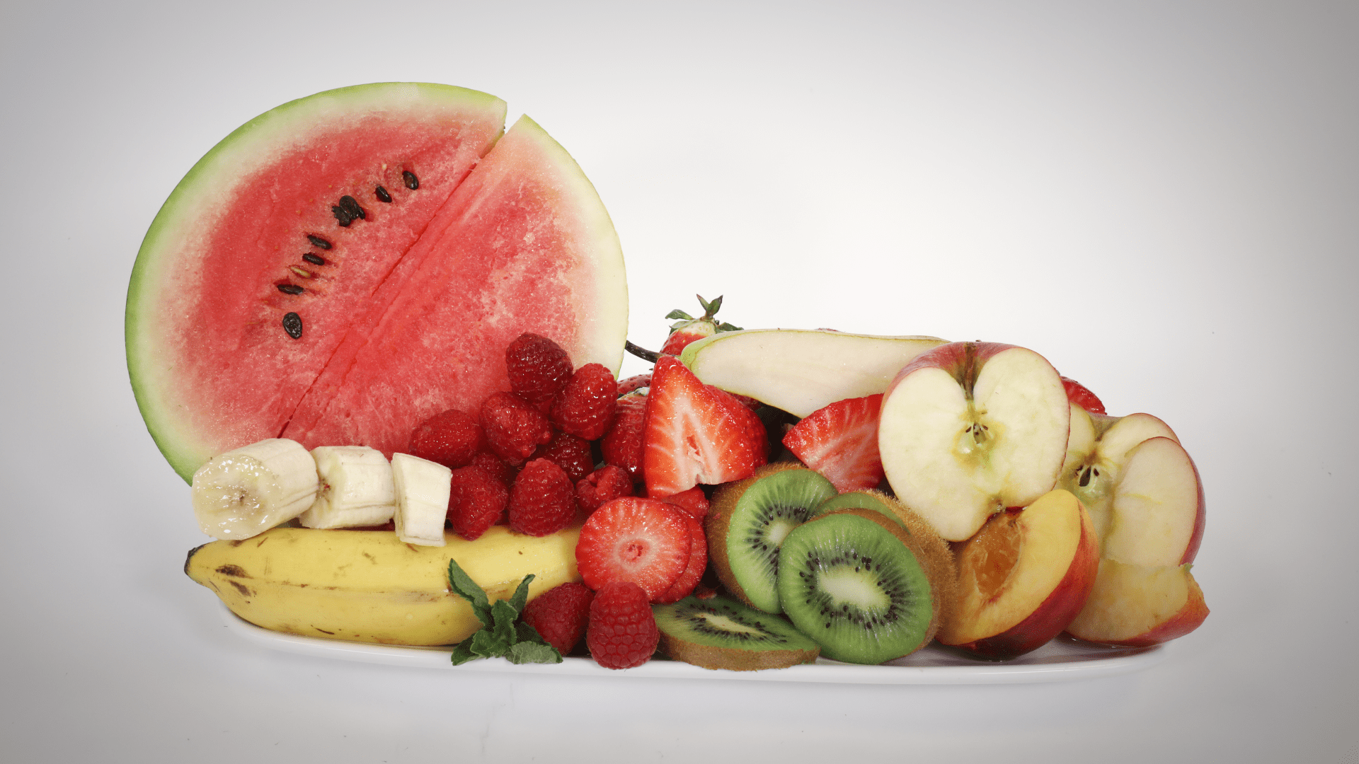 Image of a display of fresh fruit cut up or sliced, including watermelon, banana, raspberries, strawberries, kiwi and apple