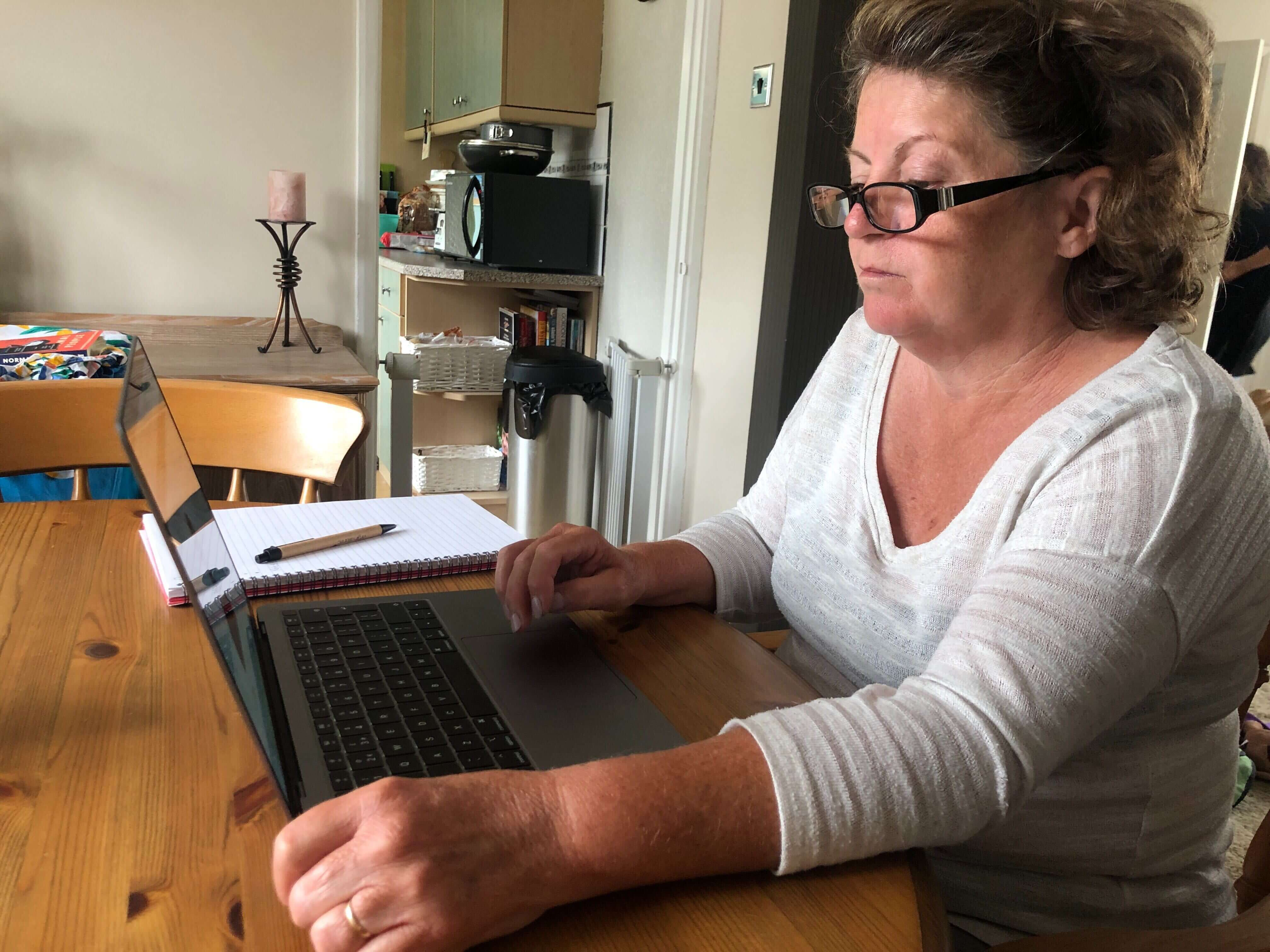 Debbie sat at her laptop at a table completing online training for the care certificate