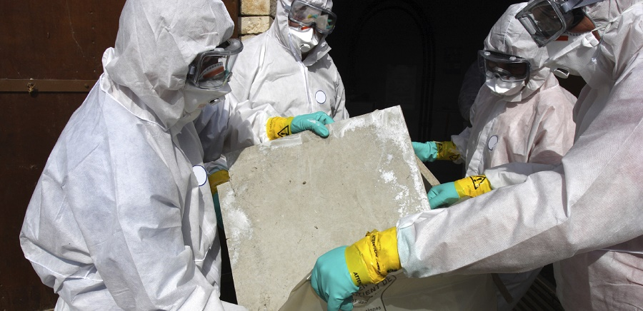 4 people in Asbestos Suits removing some Asbestos
