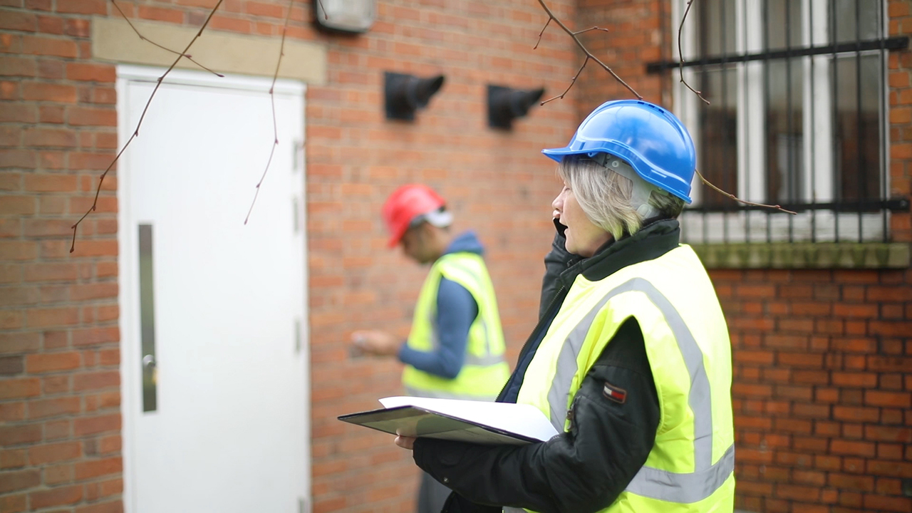 A man and woman in high visibility jackets at a work site
