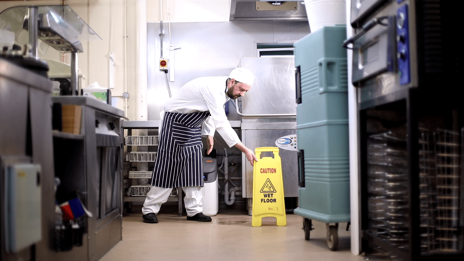 Chef in the kitchen putting out a 'caution wet floor' sign, taken from iHASCO's food safety and hygiene course.