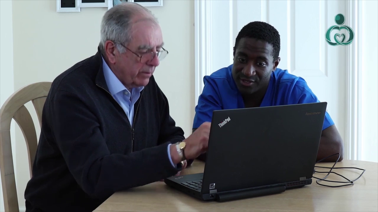 Carer sat with a resident with a laptop