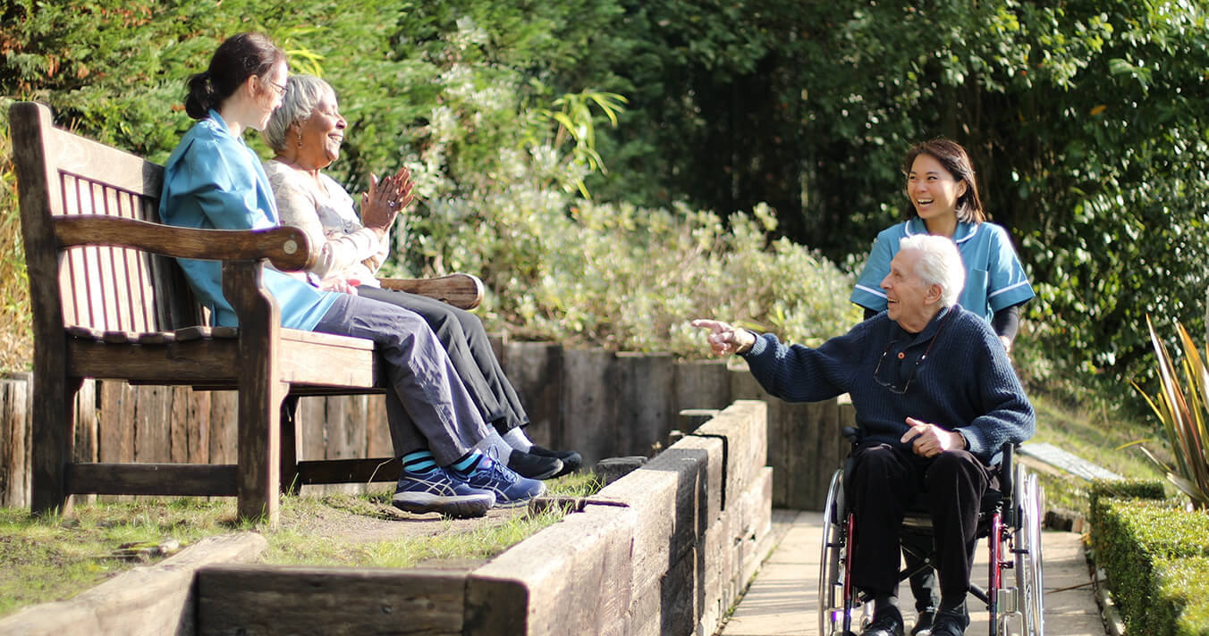 A photo of two carers looking after two residents