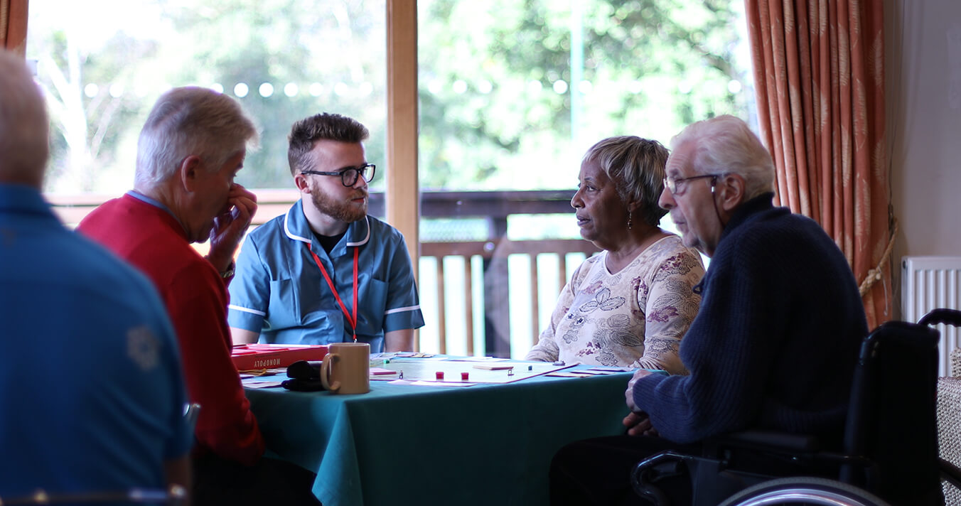 A photo of a carer and residents sitting around a table playing a board game.
