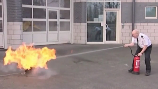 Fire Warden Training in Care. Chapter 4: A fire warden uses an extinguisher on a fire in the foreground
