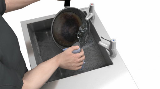 Person cleaning a pan with hot water for food safety and hygiene level 1