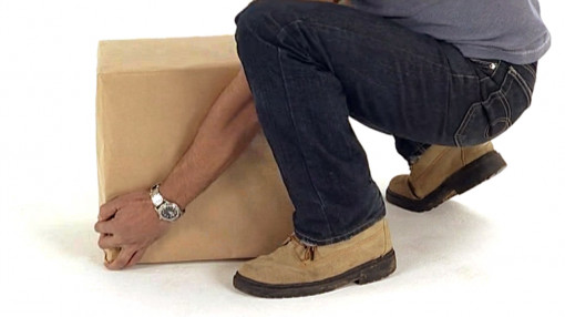 A figure crouching to pick up a package to show correct manual handling