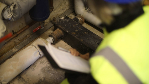 Person with a clipboard looking at a potential asbestos hazard