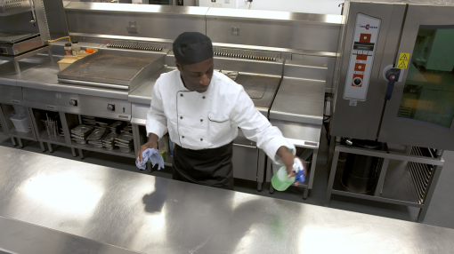 A chef cleaning down the surfaces