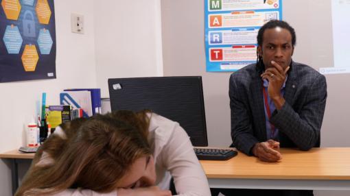 Teacher looks concerned whilst student is slumped over desk